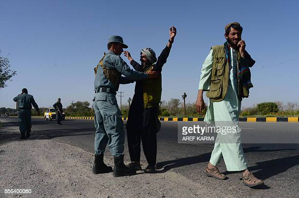 Afghan security forces search a passenger at a checkpoint after Taliban militants attacked a group of foreign tourists in western Herat province on...