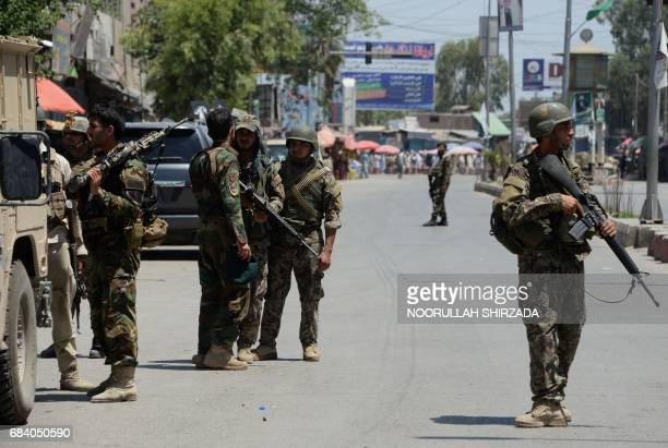 Afghan security forces stand at the site of suicide bombing in Jalalabad on May 17 2017 Suicide bombers stormed the national television station in...