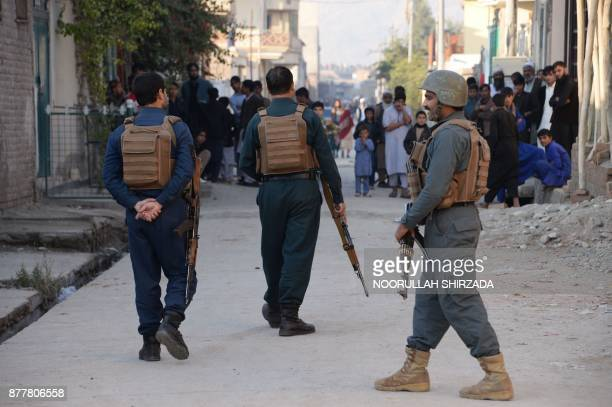 Afghan security forces stand guard near the site of a suicide attack in Jalalabad on November 23 2017 A suicide bomber struck at a crowd of people in...