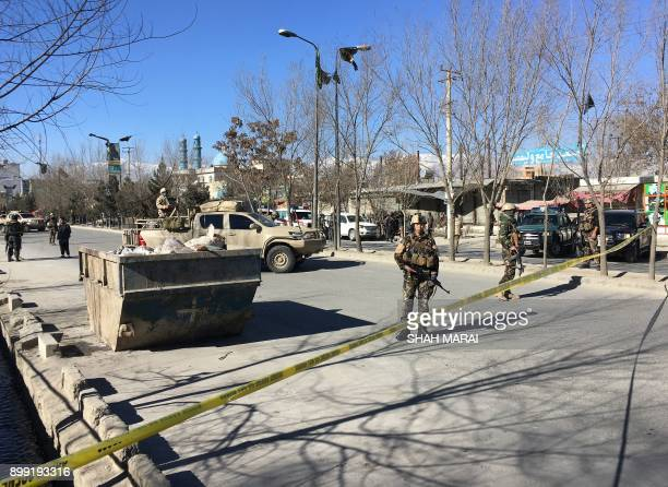 TOPSHOT Afghan security forces stand guard near the site of multiple blasts in Kabul on December 28 2017 At least five people were killed and many...