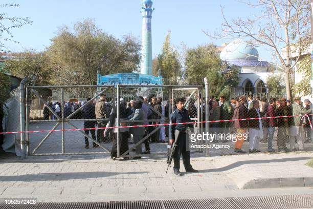 Afghan security forces stand in guard as Afghan people stand in line to cast their votes during the parliamentary elections in Kabul Afghanistan on...