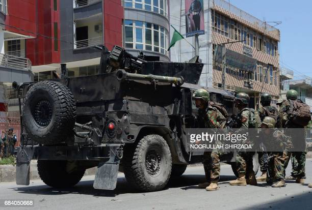 TOPSHOT Afghan security forces take up a position at the site of suicide bombing in Jalalabad on May 17 2017 Suicide bombers stormed the national...