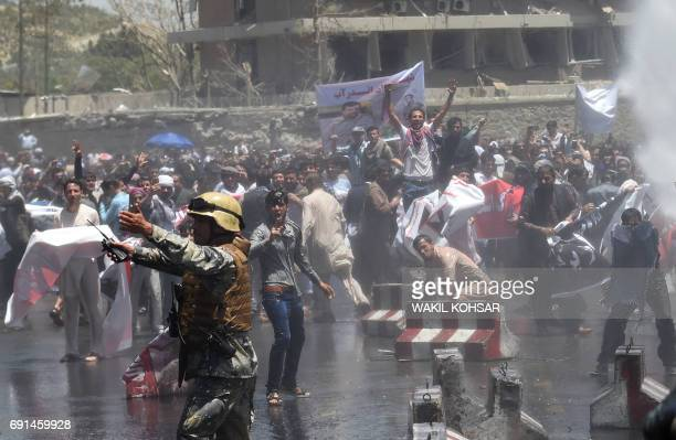 TOPSHOT Afghan security forces use water canons to disperse protesters during clashes at a protest against the government following a catastrophic...