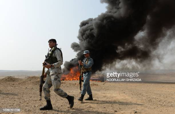 Afghan security forces walk near a pile of burning drugs and alcohol on the outskirts of Jalalabad on September 24 2018 Afghan authorities burned...