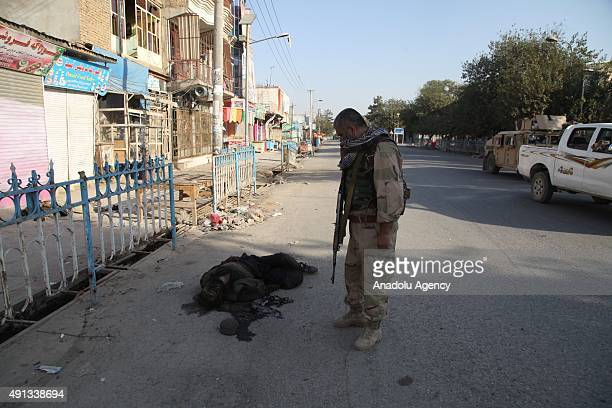 Afghan security forces walk past a Taliban fighter's dead body after retaking Kunduz from the Taliban in Kunduz city north of Kabul Afghanistan on...