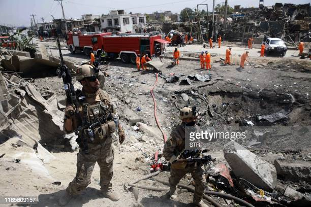 Afghan security forces walks as municipal workers gather to clean up near the crater from where a tractor packed with explosives exploded the night...