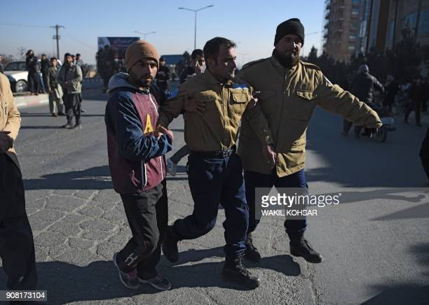 TOPSHOT Afghan security from a private company assist an injured colleague near the Intercontinental Hotel following an attack by gunmen in Kabul on...