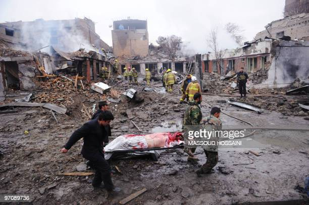 Afghan security officers carry a man's body on a stretcher from the site of a gun battle as firemen inspect the debris from a blast in the Share Naw...