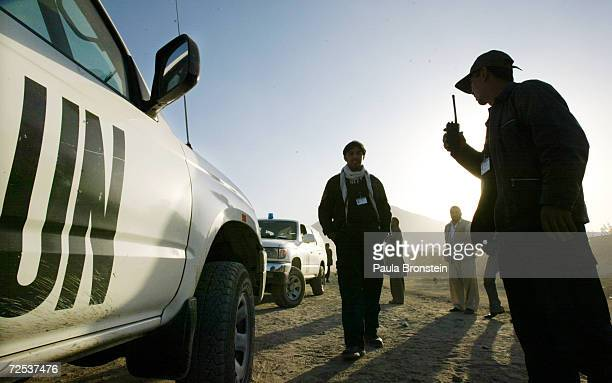 Afghan security officers stand in front of a United Nations vehicle where three foreign election workers with the joint UN mission were kidnapped...
