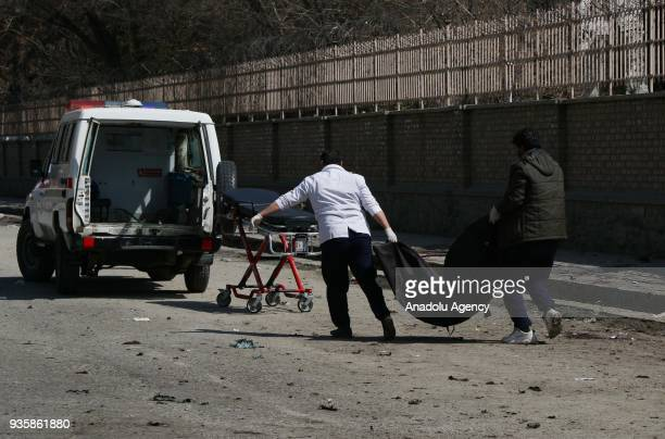 Afghan security officials carry a body after a suicide bomb blast that targeted a shrine visited by Shi'ite Muslims as the country observes the...