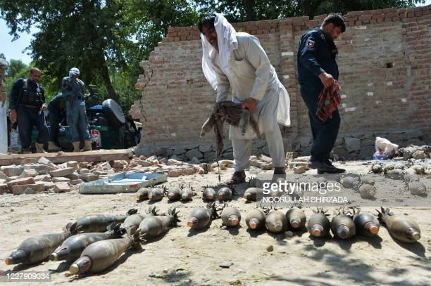 Afghan security officials inspect seized weapons near a damaged residential house from where a group of Islamic State gunmen were firing mortar...