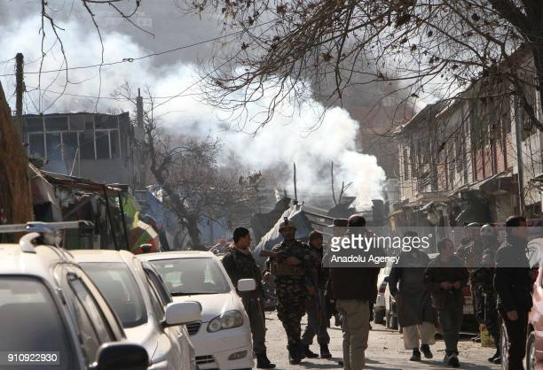Afghan security officials inspect the blast side in Kabul Afghanistan on January 27 2018 At least 40 people were killed and 140 others injured after...