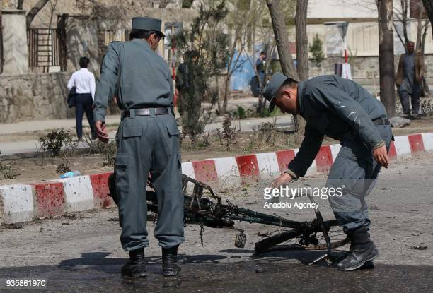 Afghan security officials inspect the scene of a suicide bomb blast that targeted a shrine visited by Shi'ite Muslims as the country observes the...