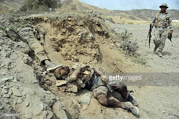 Afghan security personel walk near THE bodies of Taliban fighters after a clash with Afghan security forces in Torkham on September 2 2013 A group of...