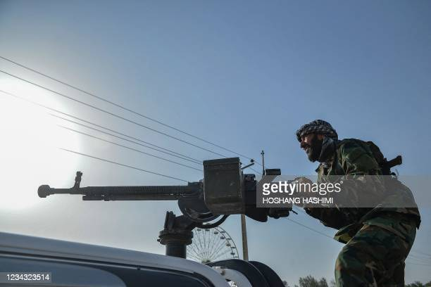 Afghan security personnel and Afghan militia fighting against Taliban, stand guard in Enjil district of Herat province on July 30, 2021.