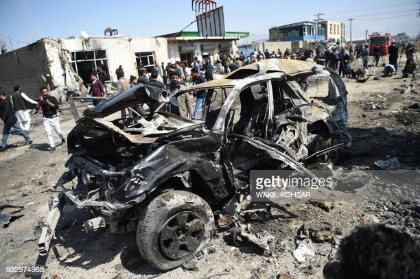 TOPSHOT Afghan security personnel and civilians gather next to a damaged car at the site of a car bomb attack in Kabul on March 17 2018 A Taliban...