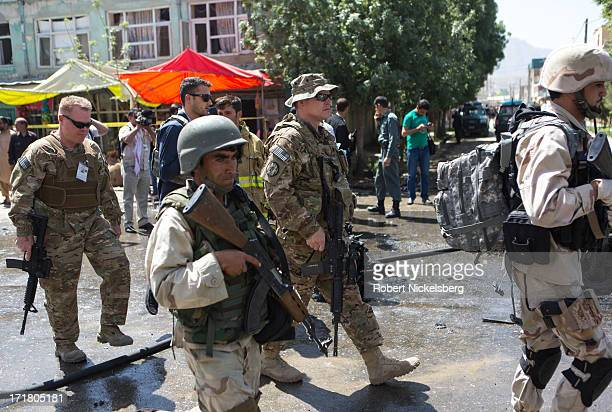 Afghan security personnel and U.S. Military forces walk through the damage left behind by a suicide car bomb explosion May 16, 2013 in Kabul,...