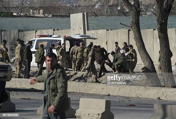 Afghan security personnel carry a bomb victim at the site of a suicide car bomb next to a police base in Kabul on February 1 2016 A suicide car bomb...