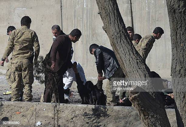 Afghan security personnel carry a victim at the site of a suicide car bomb next to a police base in Kabul on February 1 2016 A suicide car bomb...