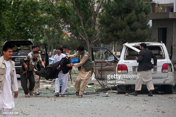 Afghan security personnel carry a victim at the site of a suicide attack that struck the convoy of presidential candidate Abdullah Abdullah on June 6...
