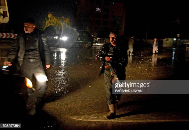 Afghan security personnel check a vehicle along a street after an unknown number of assailants mounted the attack from a building close to the Indian...