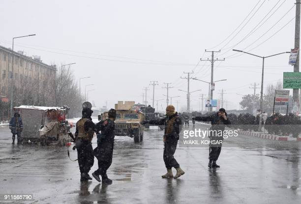 Afghan security personnel detain a suspect as they guard the site of an attack near the Marshal Fahim Military Academy base in Kabul on January 29...