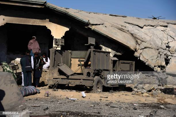 Afghan security personnel gather at the site of a suicide attack at a police compound in Maiwand district of Kandahar province on December 22 2017 A...