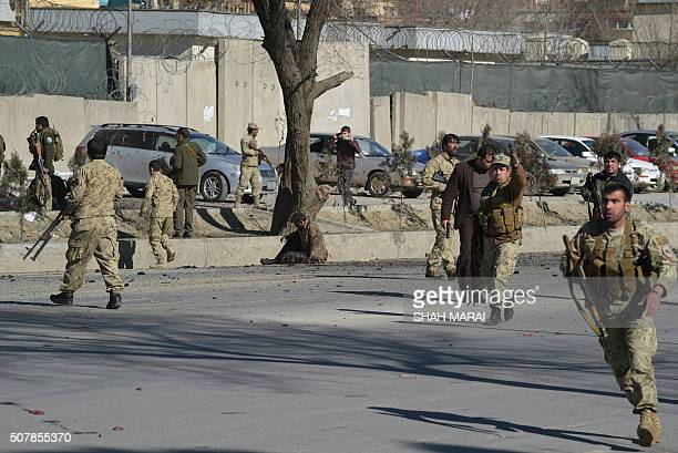 Afghan security personnel gather at the site of a suicide car bomb next to a police base in Kabul on February 1 2016 A suicide car bomb rocked a...