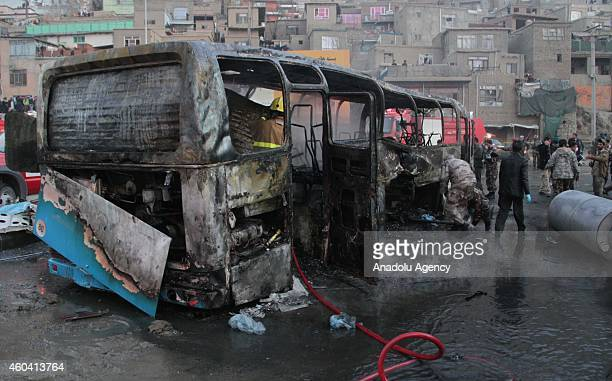 Afghan security personnel inspect a damaged bus at the site of a suicide attack by the Taliban in Kabul Afghanistan on December 13 2014 The suicide...
