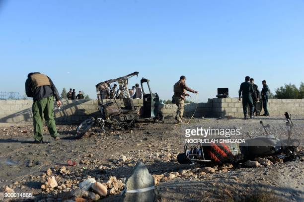 Afghan security personnel inspect the scene of a suicide attack that targeted a funeral ceremony in Jalalabad on December 31 2017 A suicide attacker...