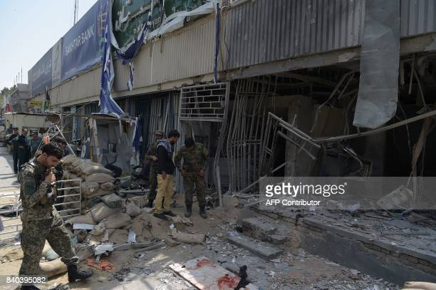 Afghan security personnel inspect the site of a suicide attack outside a bank near the US embassy in Kabul on August 29 2017 A suicide bomber blew...