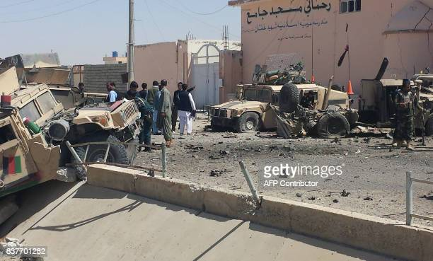 Afghan security personnel inspect the site of a suicide attack near the main police headquarters in Lashkar Gah capital of Helmand province on August...