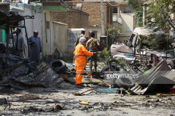 Afghan security personnel inspect the site of an explosion targeting the convoy of Afghanistan's vice president Amrullah Saleh in Kabul on September...