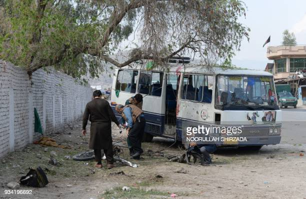Afghan security personnel inspect the site of bomb blast in Jalalabad on March 19 2018 A bombrigged motorbike exploded near a political rally in...