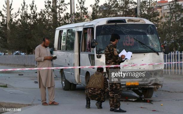 Afghan security personnel investigate a damage bus carrying employees of Khurshid TV at the site of a sticky bomb blast in Kabul on August 4 2019 At...