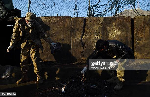TOPSHOT Afghan security personnel investigate the site after a suicide attacker detonated himself at the entrance to a police base in Kabul on...