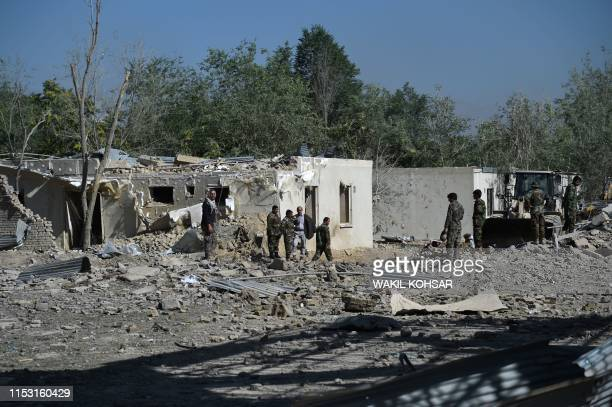 Afghan security personnel investigate the site of a Taliban car bomb attack in Kabul on July 2 a day after the deadly blast at the Defense Ministry's...