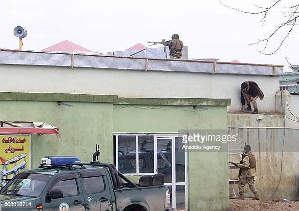 Afghan security personnel keep watch along after an unknown number of assailants mounted an attack from a building close to the Indian consulate in...