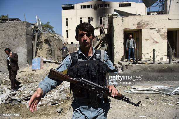 Afghan security personnel keep watch in front of the entrance to the charity organisation following a car bomb blast that targeted the CARE...