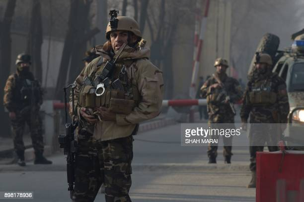 Afghan security personnel keep watch near the site of a suicide attack in Kabul on December 25 2017 A suicide attacker on foot blew himself up near a...