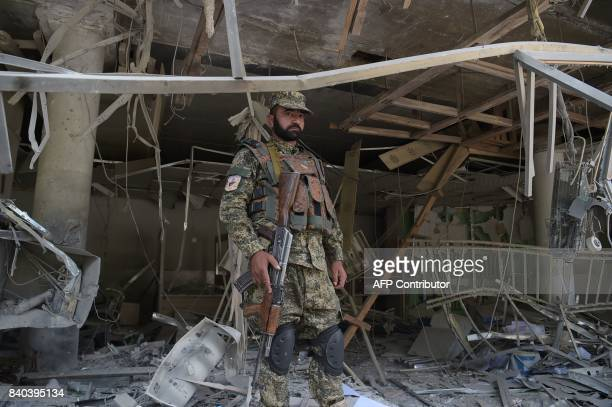 A Afghan security personnel keeps watch at the site of a suicide attack outside a bank near the US embassy in Kabul on August 29 2017 A suicide...