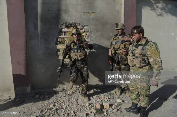 Afghan security personnel leave through a hole of a perimeter wall after gunmen disguised as policemen stormed a television station in Kabul on...