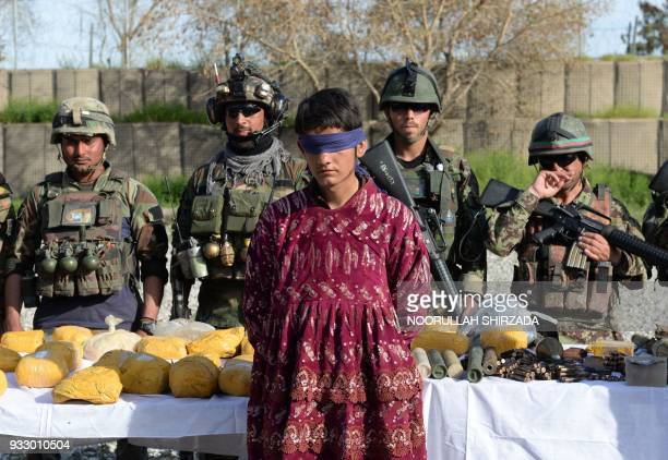 Afghan security personnel present a Taliban fighter dressed as a woman to the media at the Afghan National Army headquarters in Jalalabad on March...