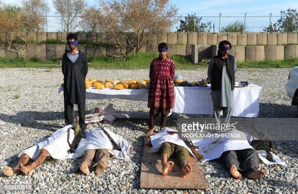 Afghan security personnel present to the media three Taliban fighters and the bodies of otther Taliban fighters lying on the ground at the Afghan...