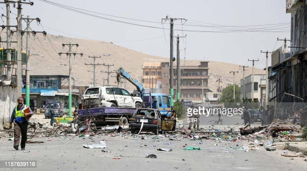 Afghan security personnel remove a damage vehicle at the site following a suicide bombing in Kabul on July 25 2019 At least 10 people including...