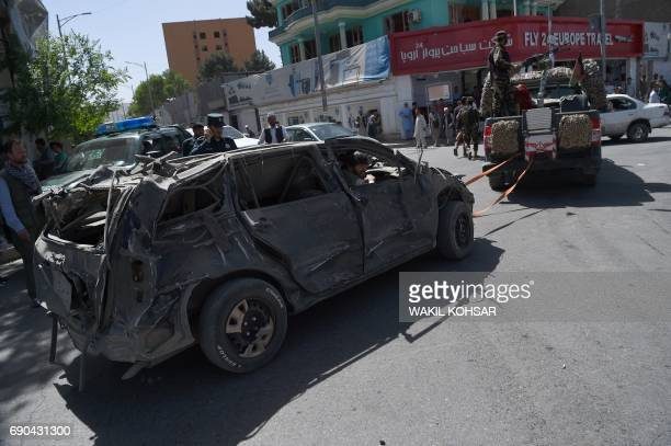 Afghan security personnel remove a damaged vehicle from the site of a car bomb attack in Kabul on May 31 2017 At least 80 people were killed and...