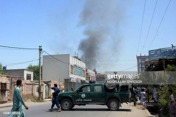 Afghan security personnel secure a road as smoke billows from the site of suicide attack as an ongoing attack between Afghan security force and...