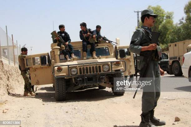Afghan security personnel sit on atop an armoured vehicles amid an ongoing battle with Taliban militants in the Gereshk district of Helmand province...