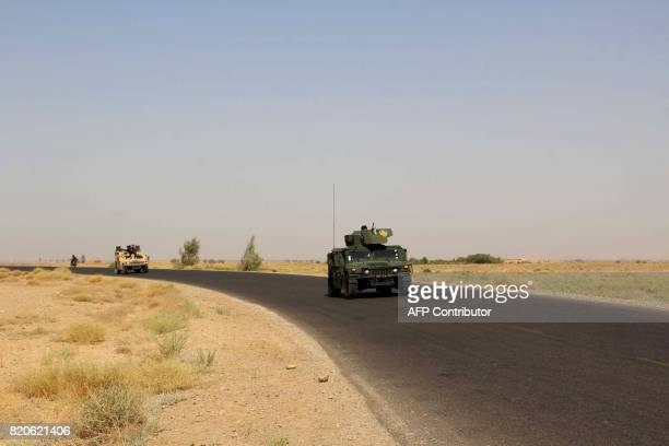 Afghan security personnel sit on their armoured vehicles amid an ongoing battle with Taliban militants in the Gereshk district of Helmand province on...