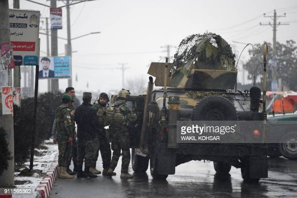 Afghan security personnel stand by an armoured vehicle near the site of an attack near the Marshal Fahim Military Academy base in Kabul on January 29...